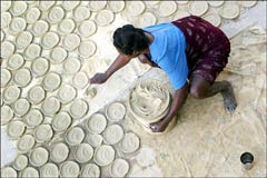 """Amid all the disturbing images in our world of late, one photograph in the May 5th, 2004 New York Times still stands out. The bleak caption was """"A woman in Fort Dimanche laying out biscuits to dry, biscuits made of butter, salt, water and dirt. The Haitians face shortages of food and electricity."""" (photograph from New York Times, May 5, 2004)"""
