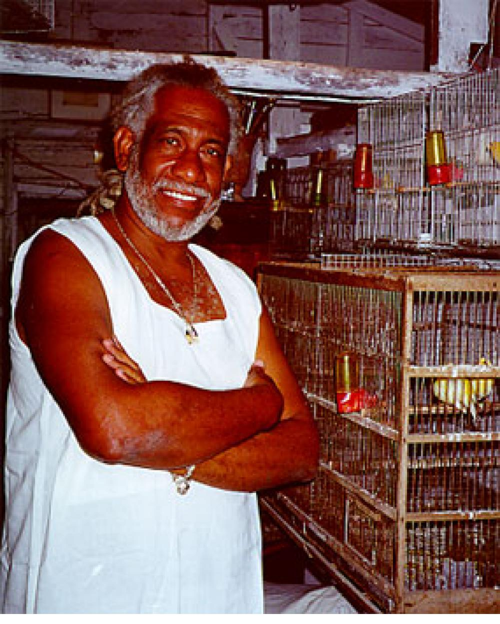 Painter Manuel Mendive in his studio with some of his birds.