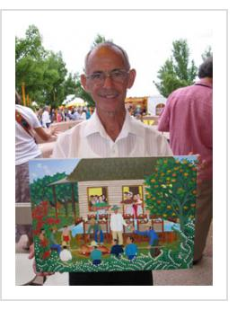 "Luis Joaquin Rodriguez Arias with one of his paintings, ""Navidad 1949"" at the 2014 International Folk Art Market. ( Photograph © Anthony Hart Fisher)."