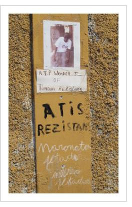 """""""R.I.P. Wender T. of Timoun Rezistans"""" - Sign posted in the Timoun community, January, 2014. (Photograph © Anthony Hart Fisher 2014)."""