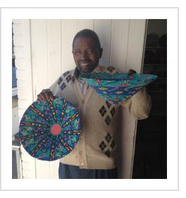 "Solomon Sima with two of his distinctive ""lampshade""-design baskets."
