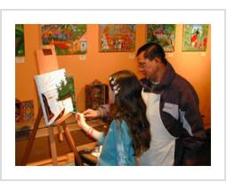 Ignacio Fletes Cruz instructs a young artist at Indigo Arts Gallery. February 3rd, 2007.
