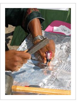 Aluminum-relief artist Toyin Folorunso demonstrates his art in Santa Fe. July, 2007 (photo by A H Fisher).