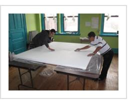 Ignacio Fletes Cruz and a student smooth the gesso on the canvas for the mural at Centro de Estudiantes, April 8 2011.