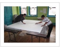 Ignacio Fletes Cruz and a student smooth the gesso on the canvas for the mural at Centro de Estudiantes, April 8 2011.
