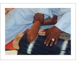 Ousmane Ganamé pounding indigo fabric smooth to finish it. (Photograph © Anthony Hart Fisher 2003).