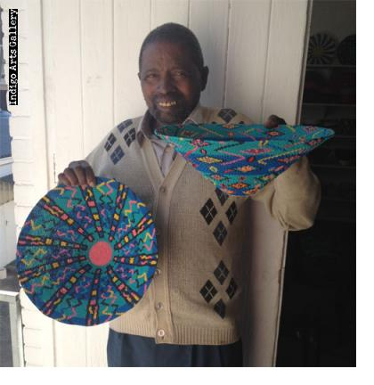 """Solomon Sima with two of his distinctive """"lampshade""""-design baskets, #zwb-604 in his right hand."""